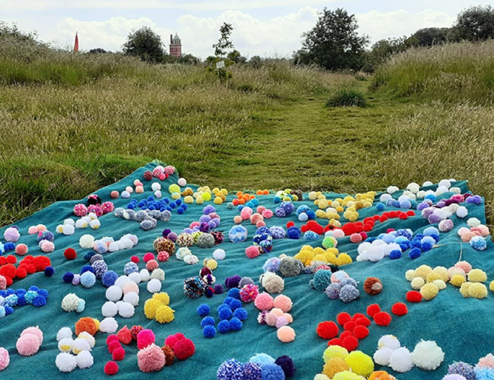 A green rug covered in pompoms is laid out in a field with Whitchurch Hospital visible in the background.