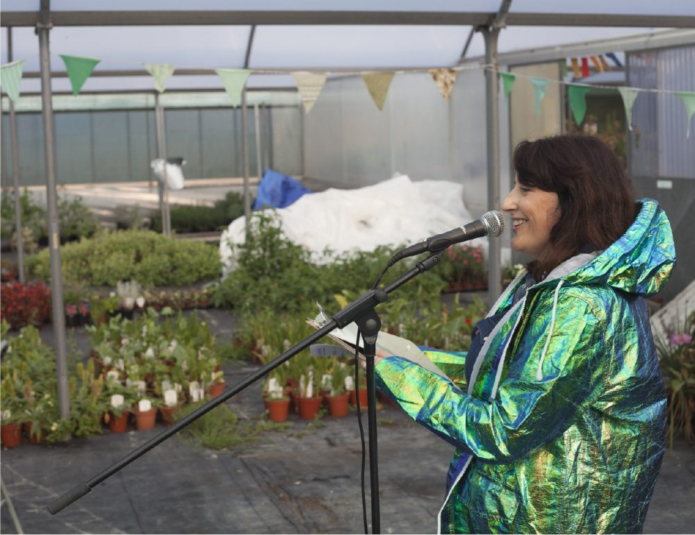 A smiling woman in a shiny green jacket speaks into a microphone. She is standing in a polytunnel full of plants.