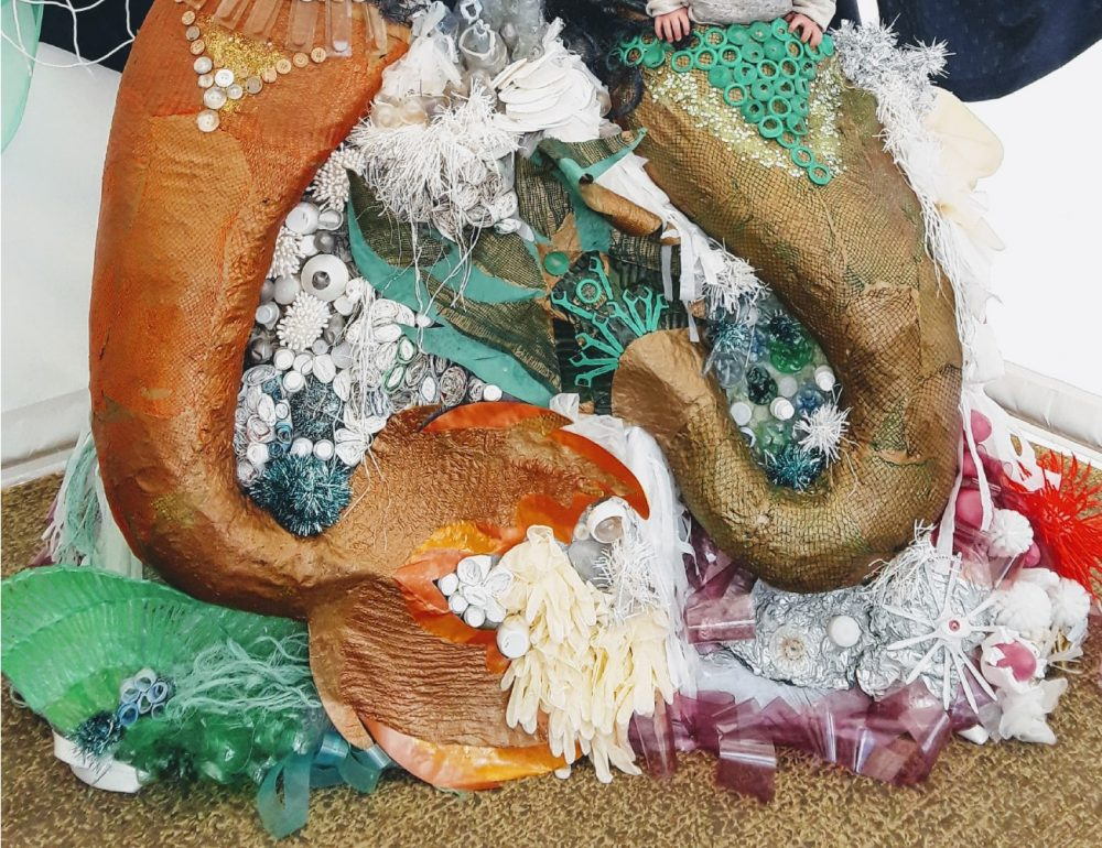 Two mermaid tails made from beach litter