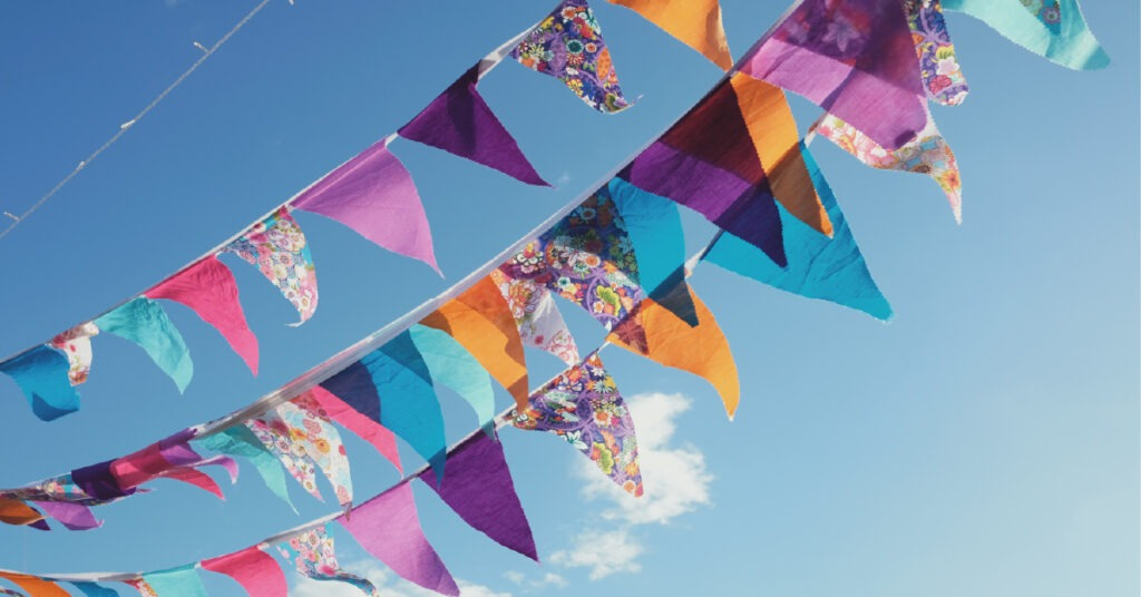 Colourful bunting flags against a blue sky.