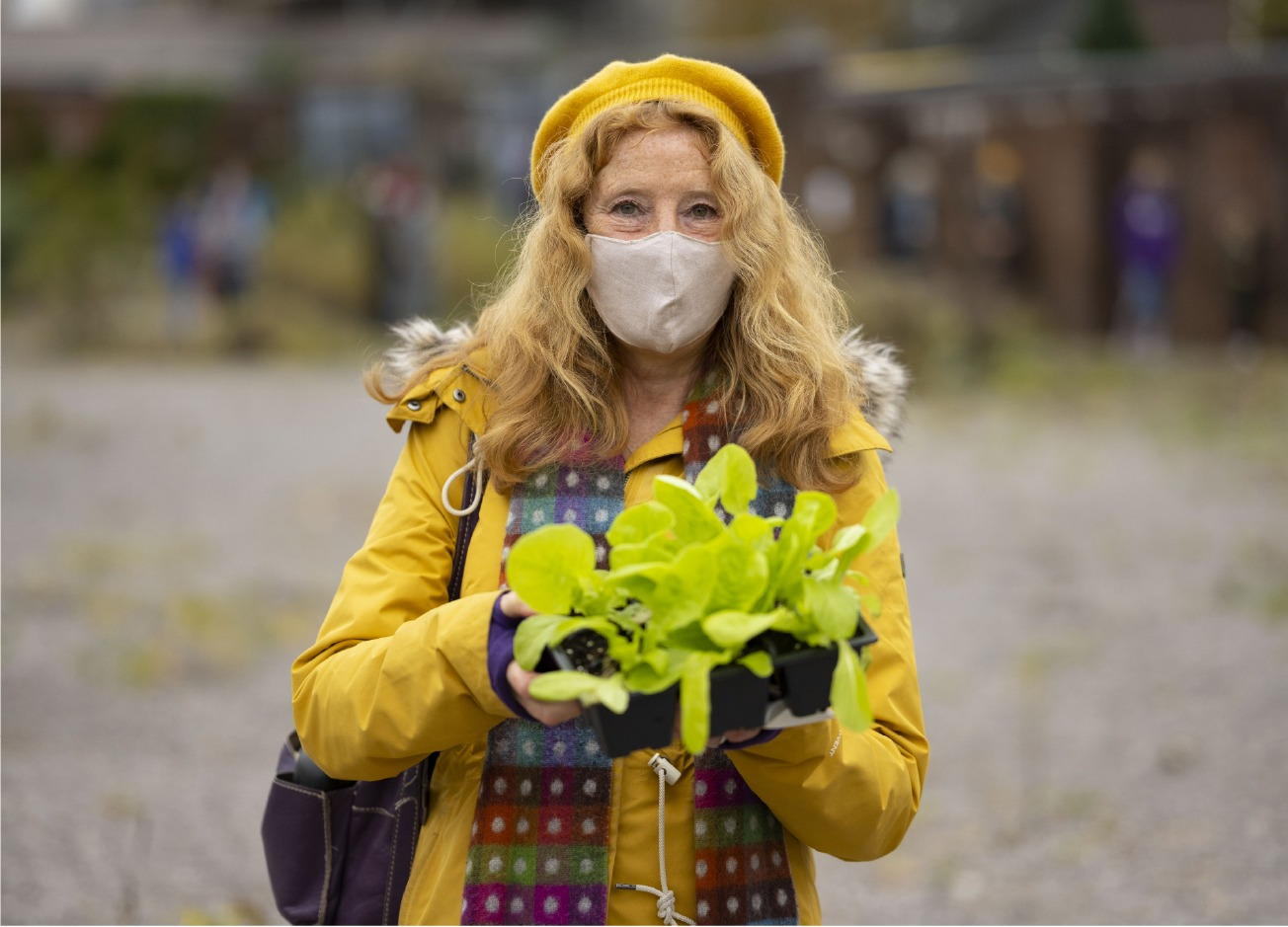 A woman in a yellow coat and hat and wearing a mask holds a tray of salad.