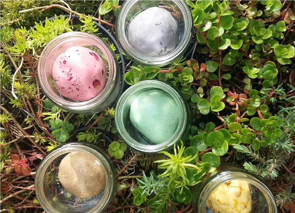 Jars of colourful homemade playdough sit on a surface of foliage.