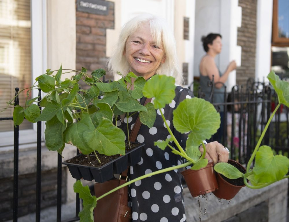 A smilling woman hold trays of plants in front of terraced houses.