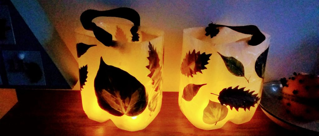 Two homemade lanterns, upcycled from milk bottles and decorated with leaves
